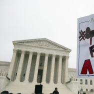 A demonstrator with the American Association of University Women (AAUW) holds a sign outside the Supreme Court in Washington, Wednesday, Dec. 9, 2015, as the court heard oral arguments in the Fisher v. University of Texas at Austin affirmative action case. (AP Photo/Cliff Owen)