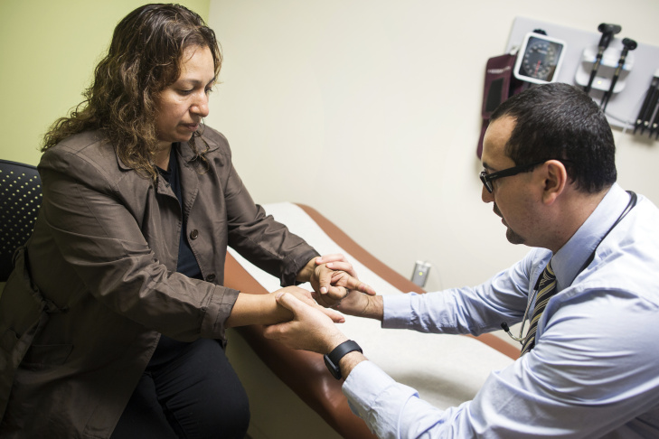 Dr. Cesar Barba treats Lourdes Flores Valdez at UMMA Community Clinic's Fremont Wellness Center in South Los Angeles. She worries her husband, who's in the U.S. illegally, could be deported.