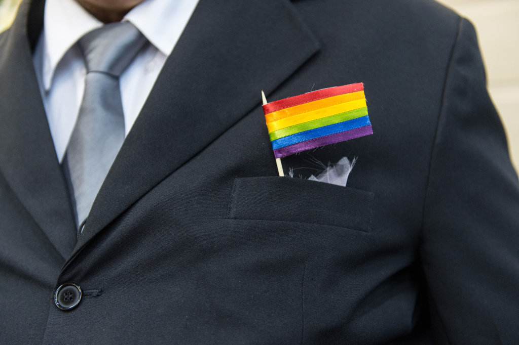 The father of a bride wears a rainbow flag during the wedding ceremony at the Court of Justice of the State of Rio de Janeiro in Rio de Janeiro, Brazil, on December 8, 2013.
