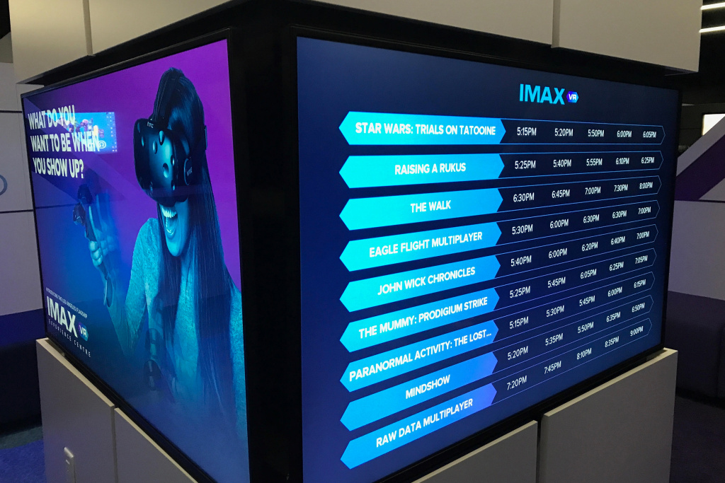 A screen displaying virtual reality experience showtimes at the IMAX VR Centre in Los Angeles.