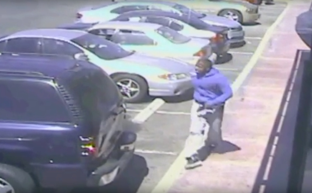 In a screenshot from a security camera video released by the Los Angeles Police Department, Carnell Snell, Jr. can be seen holding what appears to be a handgun in his left hand shortly before officers shot and killed him.