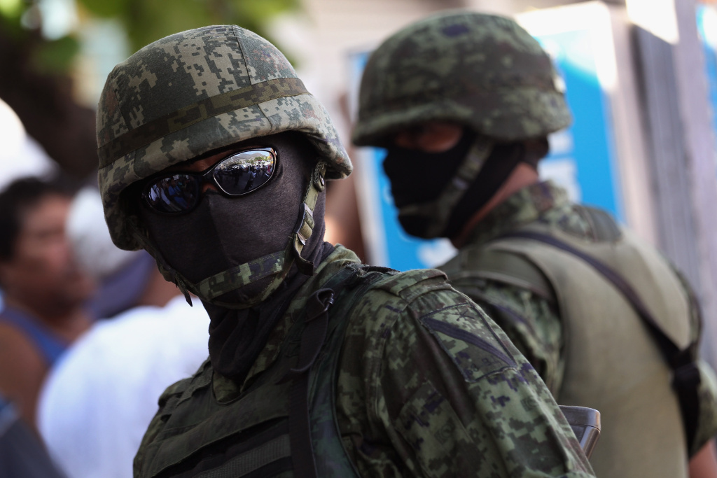 Mexican army soldiers stand guard at the site of a suspected drug execution in 2012. The government said Thursday it will give at least 50 million pesos to relatives of criminal suspects slain at a warehouse last year by soldiers.
