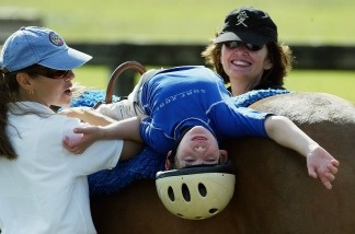Eight year-old Michael Dedrick-Dwyer, who has Cerebral Palsy and Autism, takes 30-minute ride on a horse with therapist Rebecca Reubens and volunteer Kimberly Schuman.