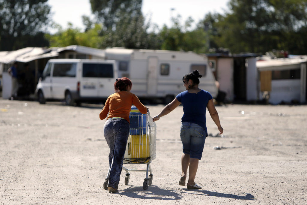 Women from the Roma community push a shopping trolley containing water toward their camp on September 9, 2012 in a camp in Sucy-en-Brie, near Paris.
