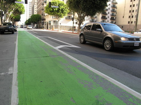 The green paint on the Downtown bike lanes is faded and peeling after only a few months.