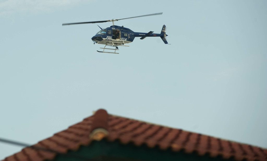 A helicopter of the Mexican state Police fly over during a raid in a house at Floresta neighbourhood in Veracruz after explosions on October 10, 2011.