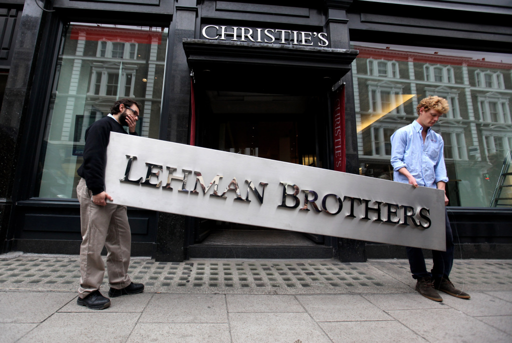 Two employees of Christie's auction house move the Lehman Brothers corporate logo, the collapsed investment bank on September 24, 2010.