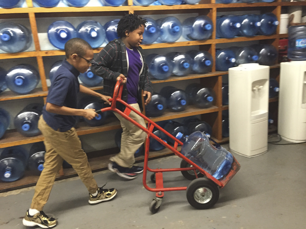 Third graders Ezekiel White (right) and Emanuel Black push a jug of water to the cafeteria at Southwest Baltimore Charter School.