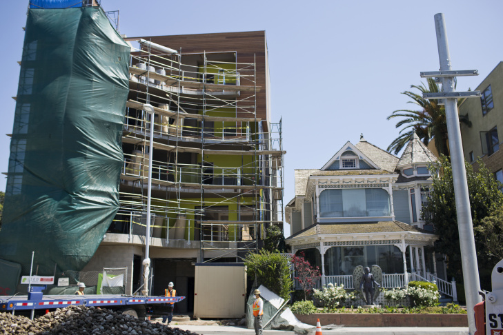 An under-construction five-story building, left, sits adjacent to a two-story Victorian house, Angel's Attic Museum, on Colorado Boulevard between Fifth and Sixth Streets in Santa Monica.