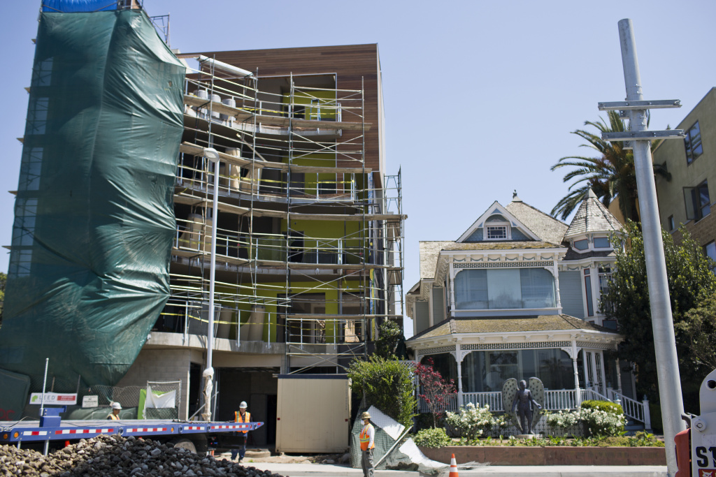 An under-construction five-story commercial building, left, sits adjacent to a two-story Victorian house, Angel's Attic Museum, on Colorado Boulevard between Fifth and Sixth Streets in Santa Monica.