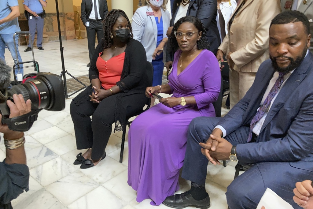 Relatives of Ahmaud Arbery including his sister Jasmine Arbery, left, and his mother Wanda Cooper-Jones, second from left, sit at the Georgia state capitol in Atlanta on Monday to witness Gov. Brian Kemp sign a law repealing citizen's arrest in Georgia.