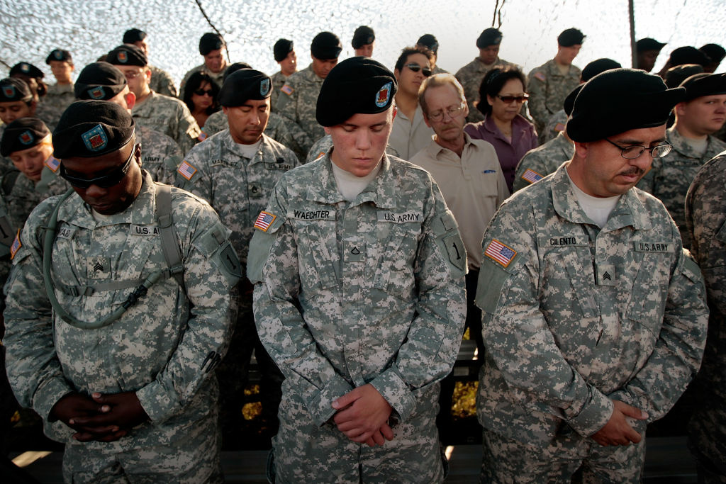 Soldiers with the 1st Infantry Division bow their heads in prayer before a deployment ceremony for another tour in Iraq August 13, 2009 at Fort Riley, Kansas.