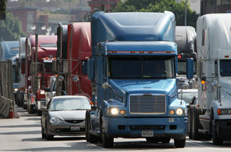 Trucks drive near City Hall to protest shipping container fees being assessed against independent truckers as part of the ports' Clean Truck Program to allow only newer, less-polluting trucks at the ports, on November 13, 2009 in Los Angeles.