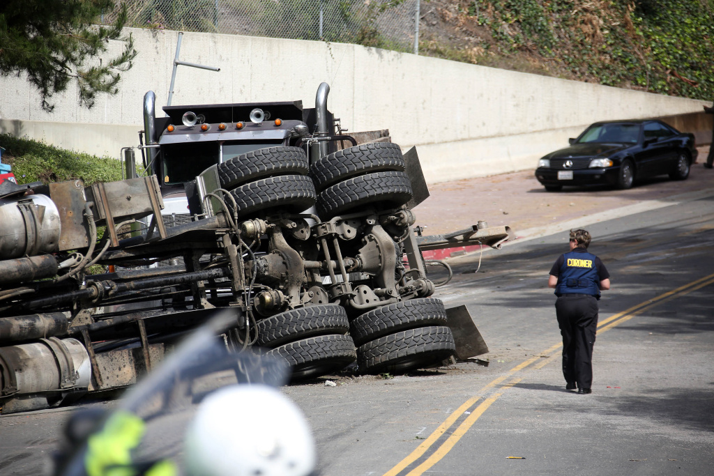 A Los Angeles Coroners official walks by the scene of a wreck Friday March 7, 2014 where a Los Angeles police officer was killed and another critically injured, when their cruiser was struck by a big rig at a Beverly Hills intersection.