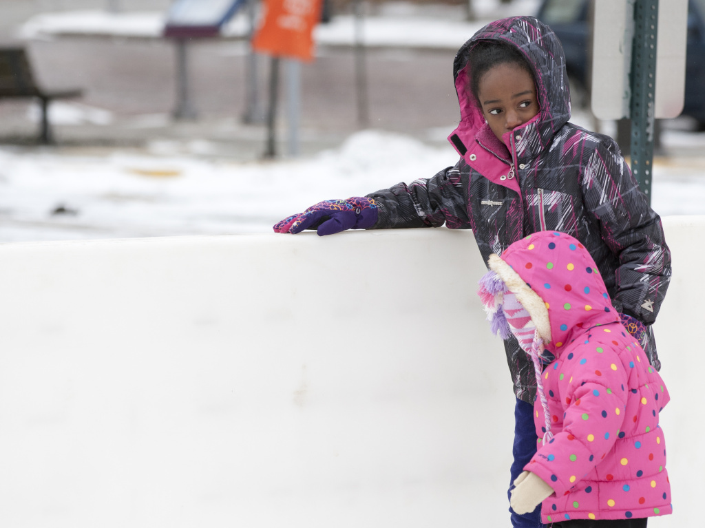 Brooklyn Hill, 3, gets help from 10-year-old Thalia Epps on as they skated in Ann Arbor, Mich. on December 30, 2014.