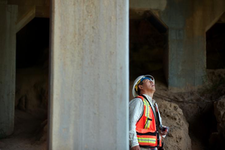 Caltrans Senior Bridge Engineer Bing Wu inspects the underbelly of a bridge that's part of Pacific Coast Highway in Manhattan Beach.