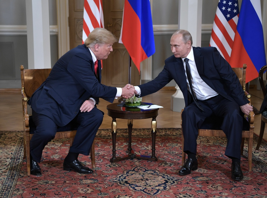 US President Donald Trump shakes hands with Russia's President Vladimir Putin (R) during a meeting in Helsinki, on July 16, 2018.