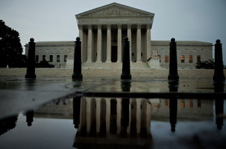 The US Supreme Court building is reflected in water August 5, 2010 in Washington, DC.