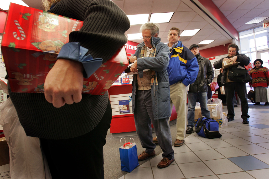 U.S. Postal Service customers wait in line to mail Christmas presents at a U.S. Post Office in this December 20, 2004 file photo taken in Washington, DC. The USPS says 10 percent more mail is anticipated between Thanksgiving and Christmas this year compared to 2014.