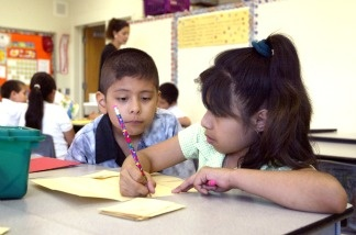 Students work together in teacher Daisy Moran's second-grade bilingual class during summer school in Chicago, Illinois.