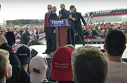 U.S. Secret Service agents surround GOP presidential candidate Donald Trump as other security officers—behind stage to left—subdue a man who attempted to rush the stage during a Trump rally in Dayton, Ohio, on March 12, 2016.