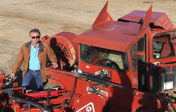 In this Dec. 27, 2016 photo, farmer Kevin Herman stands next to an almond sweeper at his ranch near Madera, Calif. Herman says that Donald Trump's campaign vow to deport millions of immigrants who are in the country illegally pushed him into buying more equipment, cutting the number of workers he'll need during the next harvest.