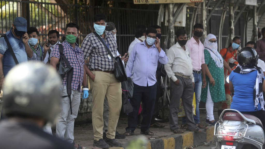 People wait for a bus in Mumbai, India, on Monday. India is reopening its restaurants, shopping malls and religious places in most of its states after a more than two-month lockdown even as the country continues to witness a worrying rise in new coronavirus infections.