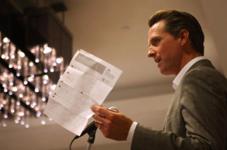 San Francisco Mayor Gavin Newsom holds the one-page application form that San Franciscans fill out for health care as he speaks at a meeting of Town Hall Los Angeles on July 9, 2009 in Los Angeles, California.