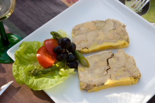 Slices of foie gras on a plate with garnish, close up
