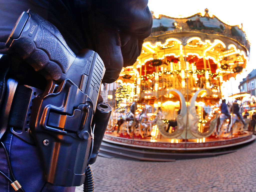 A German police officer stands next to a merry-go-round in the Christmas market in Frankfurt, Germany, Tuesday, Dec. 20, 2016 one day after a truck ran into a crowded Christmas market in Berlin killing several people. (AP Photo/Michael Probst)