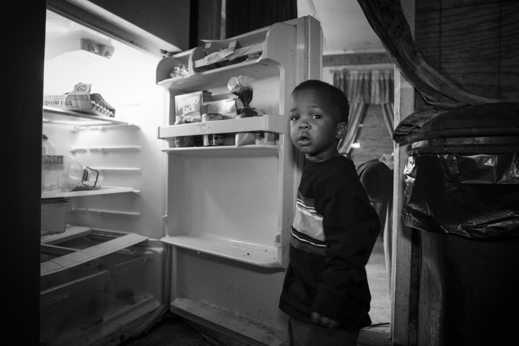 A boy opens his nearly empty fridge. The photo will be featured in a new mobile exhibit put on by Mazon, a local nonprofit.