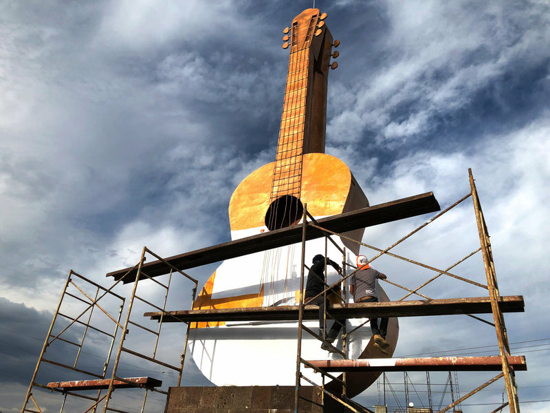 Workers cover a large bronze guitar statue in white. The statue sits at the entrance to the town of Paracho. This weekend, the town will pay tribute to German Vazquez, a former resident and master guitar maker from the town. Vazquez designed the white guitar featured in the movie