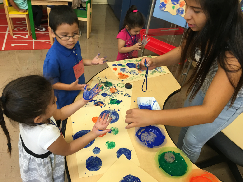 Glassell Park ETK teacher, Ms Pineda, works with a small group of six children on a sponge painting project.