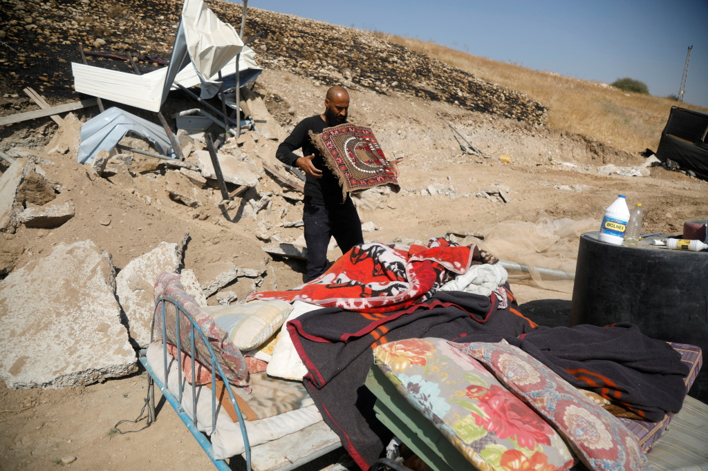 A Palestinian man collects his belongings after his structure was demolished by Israeli forces in the Jordan Valley in the Israeli-occupied West Bank October 19, 2020. Palestinian groups say another hamlet was destroyed in the same area on Tuesday.
