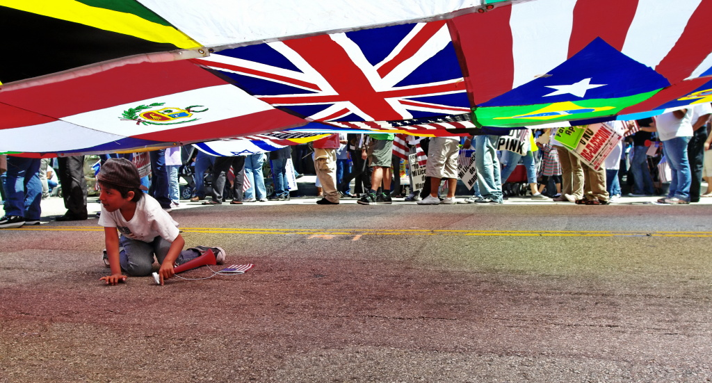 A child plays under an international display of flags at a downtown Los Angeles immigration rally. A new analysis of census data suggests that fewer immigrants arrived in the U.S. between July 2012 and July 2013 than in the previous year.
