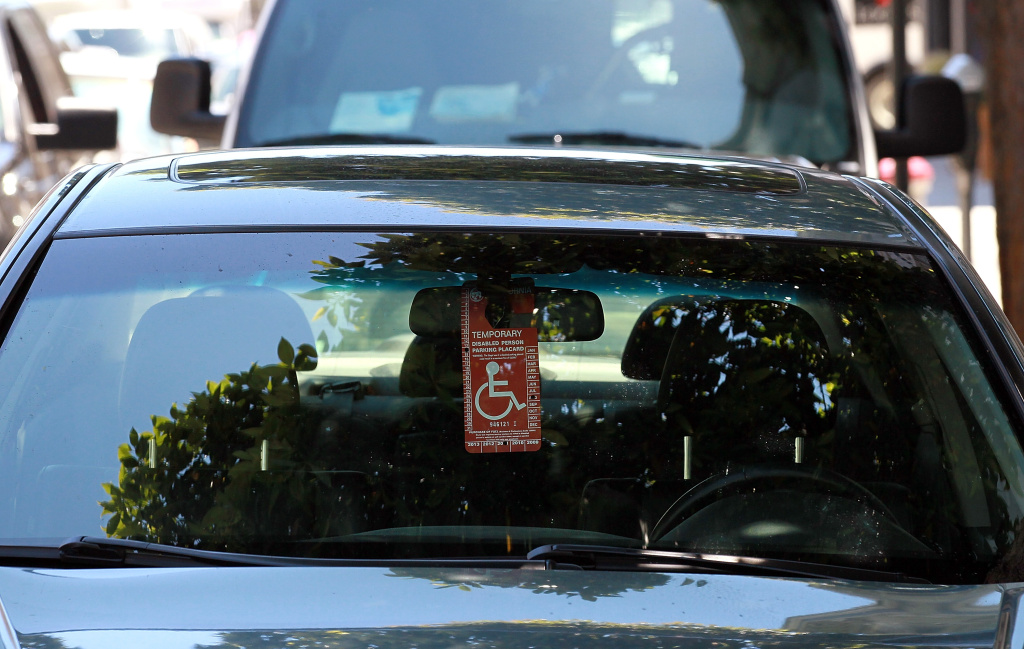 A disabled parking placard hangs from a car's rearview mirror on July 20, 2011 in San Francisco, California.