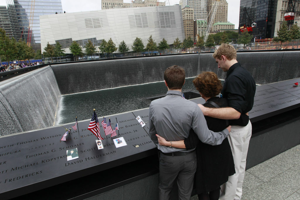 Nancy Gregory, hugs her sons Carl, left, and Gregory as they pay their respects to her husband firefighter Ken Kumpel at the National 9/11 Memorial.