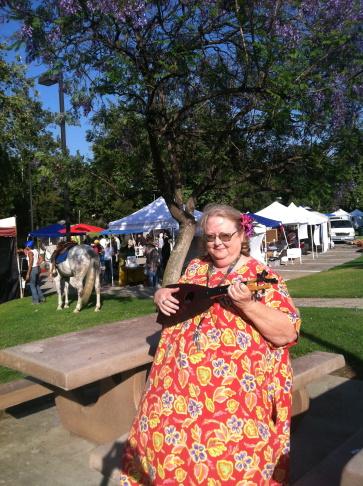 Altadena resident Donna Barnes-Roberts holds her ukulele outside the Altadena Farmers Market