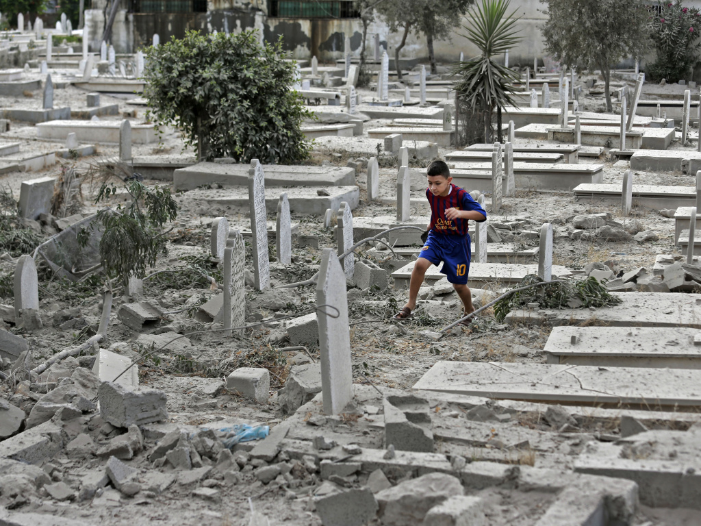 A Palestinian boy runs on rubble of damaged graves at a cemetery hit by an Israeli strike in Gaza City, on Sunday.