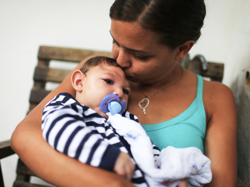 Mother Daniele Santos holds her baby Juan Pedro, who has microcephaly, on May 30, 2016 in Recife, Brazil. Researchers are now learning that Zika's effects can appear up to a year after birth.