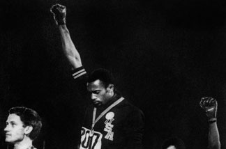US athlete Tommie Smith raises his gloved fists in the Black Power salute to express opposition to racism in the US during the US national anthem, after receiving his medal October 17, 1968 for first place in the men's 200m event at the Mexico Olympic Games.