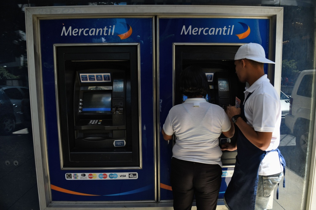 A couple withdraws money from an ATM in Caracas on August 20, 2018.