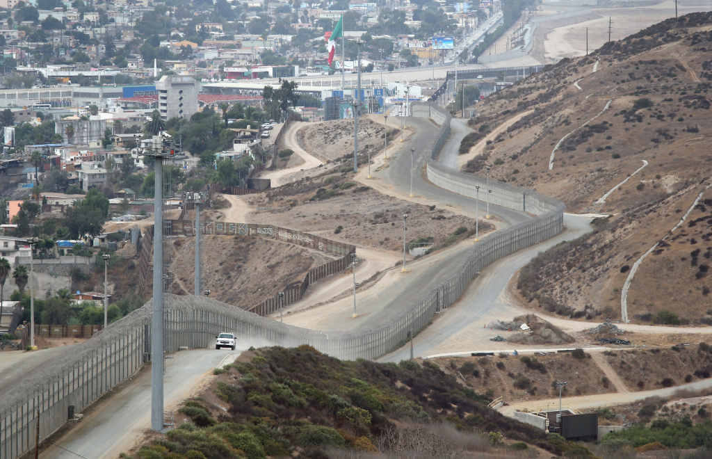 A U.S. Border Patrol agent patrols near a stretch of the U.S.-Mexico border fence on October 3, 2013 near San Ysidro, California. The fence is double in some areas, while often ceases altogether in deep ravines or mountainous areas. While hundreds of thousands of government workers were furloughed Tuesday, thousands of Border Patrol agents, air-traffic controllers, prison guards and other federal employees deemed