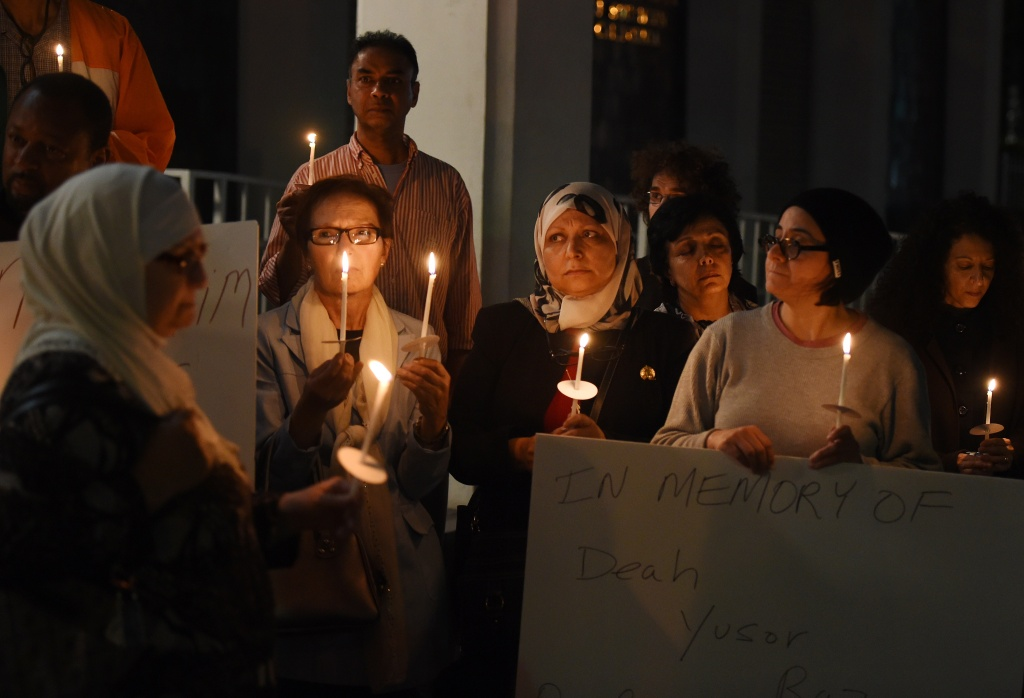 Muslims hold a candlelight vigil  at the Islamic Center of Southern California in Los Angeles on February 12, 2015  for the three Muslim students who were fatally shot in North Carolina.