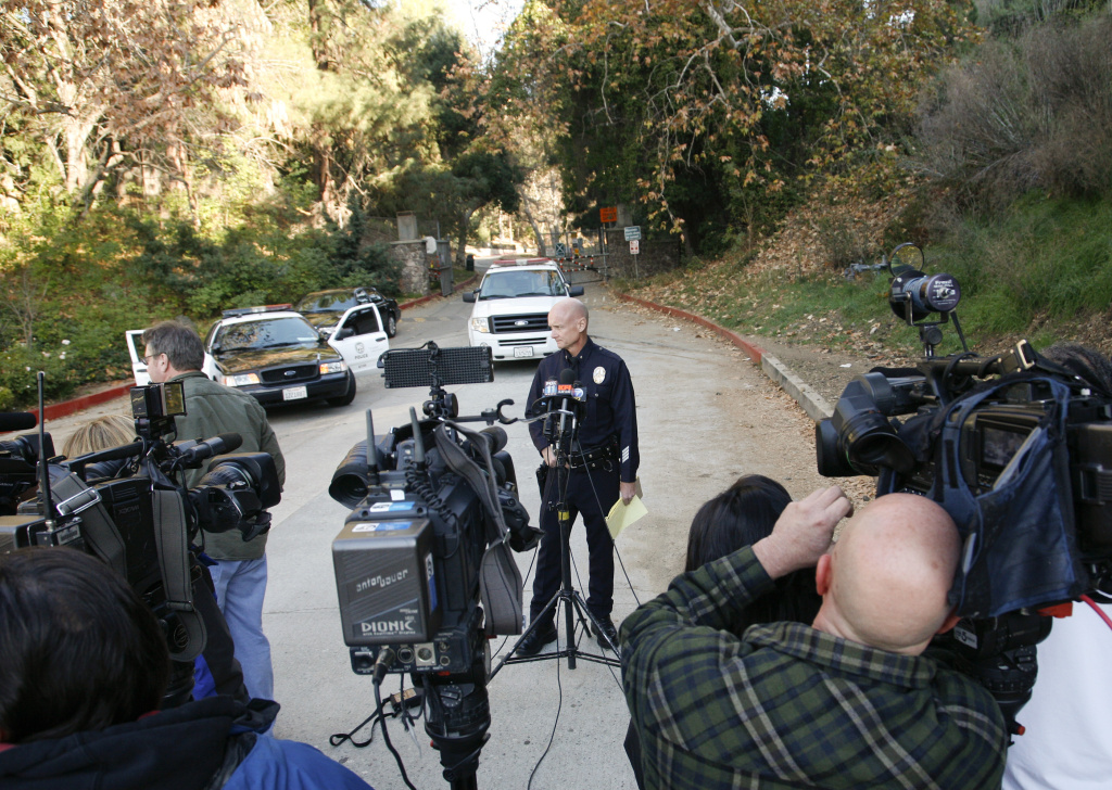 LAPD Cmdr. Andy Smith, center, prepares to speak to media in front of the Bronson Canyon Park entrance as detectives search the neighborhood below the Hollywood sign after a plastic bag containing a human head was discovered Tuesday on a nearby trail.