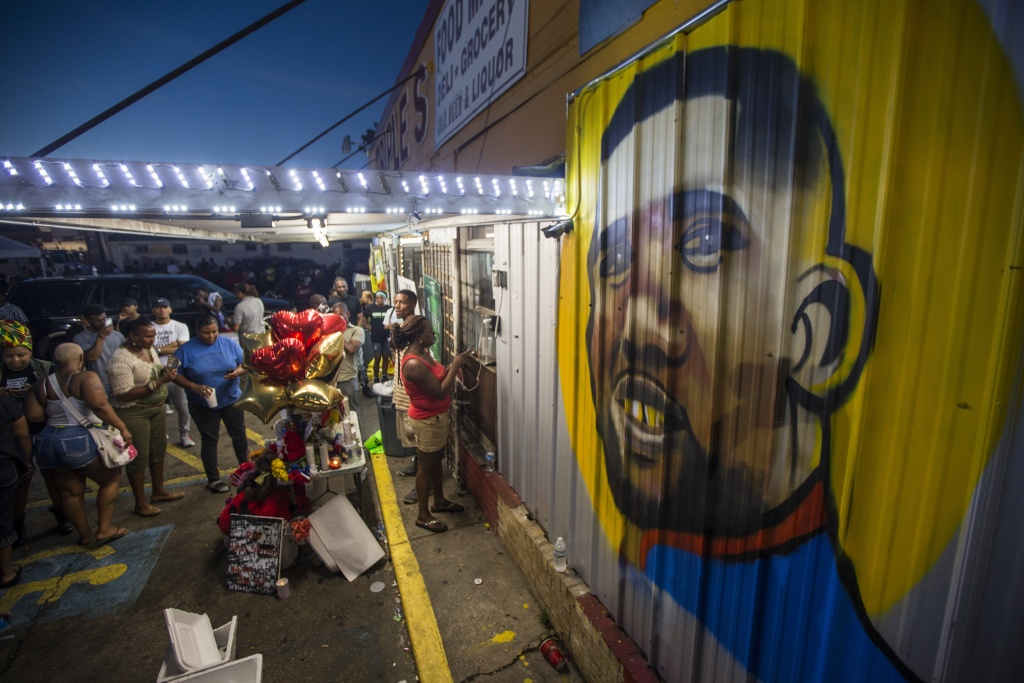 Protesters gather in front of a mural painted on the wall of the convenience store where Alton Sterling was shot and killed, July 6, 2016 in Baton Rouge, Louisiana.  Sterling was shot by a police officer in front of the Triple S Food Mart in Baton Rouge on Tuesday, July 5, leading the Department of Justice to open a civil rights investigation.