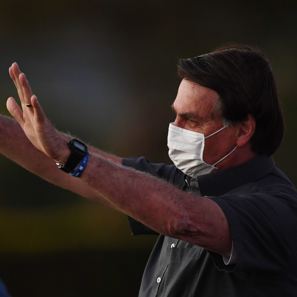 Brazilian President Jair Bolsonaro waves to supporters from the Alvorada Palace in Brasilia on Monday, the same day that two more of his Cabinet ministers were diagnosed with COVID-19.