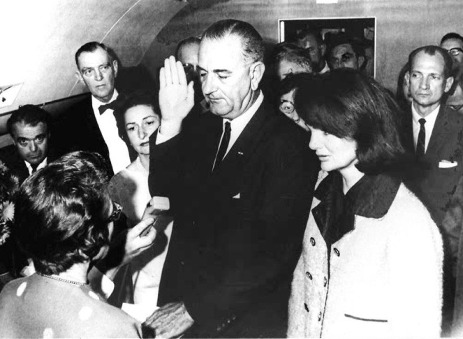 File: In this Nov. 22, 1963 file photo, Jacqueline Kennedy Onassis (R) and Lady Bird Johnson (2ndL), watch as US Vice President Lyndon Johnson (C) is administered the oath of office by Federal Judge Sarah Hughes (L) as he assumed the presidency of the US following the assassination of President John F. Kennedy in Dallas, Texas.