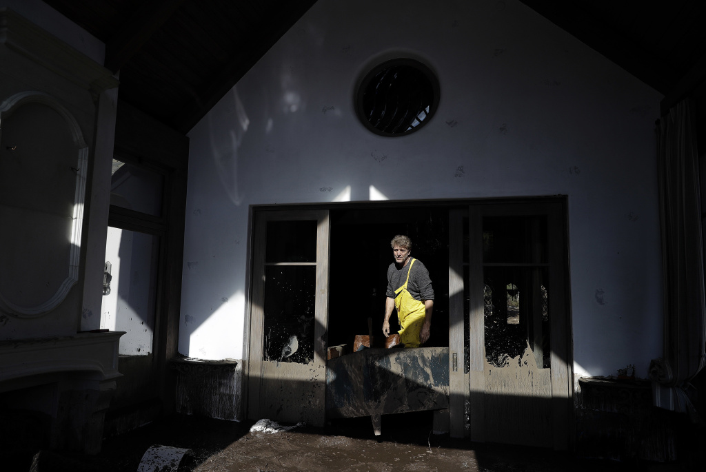 Bill Asher walks through mud in his home damaged by storms in Montecito, Calif., Thursday, Jan. 11, 2018. Rescue workers slogged through knee-deep ooze and used long poles to probe for bodies Thursday as the search dragged on for victims of the mudslides that slammed this wealthy coastal town. Some were left to wonder how they survived when neighbors didn't.