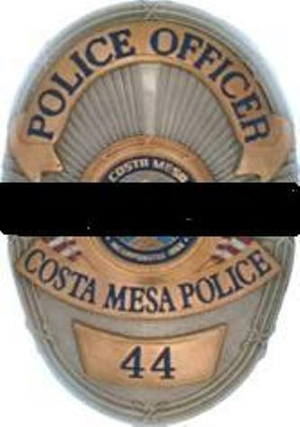 A badge from the Costa Mesa Police Department with a black band signifying the department is mourning a fallen officer.